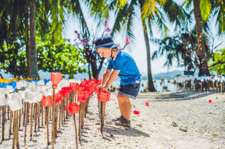Recycled colorful plastic flower and preschool boy. Flowers made from a plastic bottle. plastic bottle recycled. Waste recycling concept