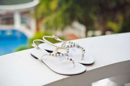 Wedding shoes on the pool background. Wedding in the tropics concept