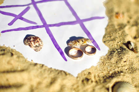 weddingrings: Tic Tac Toe and wedding rings on the beach. Wedding in the tropics concept.