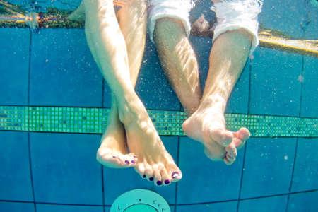 Beine von Mann und Frau im Pool unter Wasser.