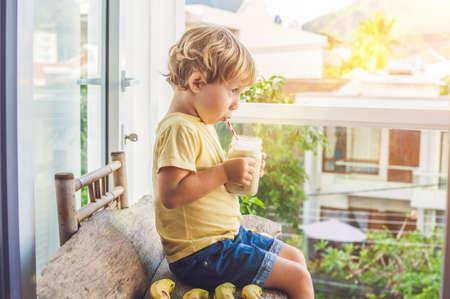 Boy holding a banana smoothie, proper nutrition concept