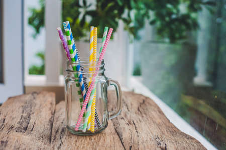 Vintage mason jar and multicolored spiral straws. wedding decor concept. Sweet table. A table with a drink concept.. Stock Photo