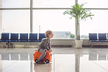Cute little boy with orange suitcase at airport. Stock Photo