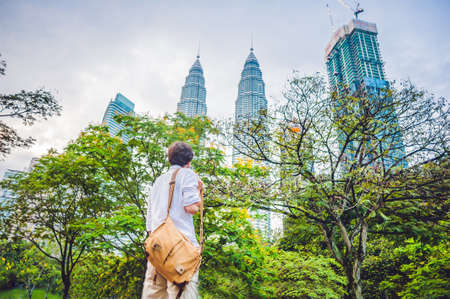 Man tourist in Malaysia looks at the Petronas Twin Towers.