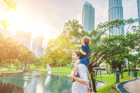 Father and son travelers in Malaysia against a background towers Patronas twins. Traveling with children concept.