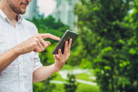 concep: Man businessman or student in casual dress using tablet in a tropical park on the background of skyscrapers. Dressing in a white shirt, beige shorts. Young handsome businessman in casual clothes is sitting outside a business district. Mobile Office concep Stock Photo