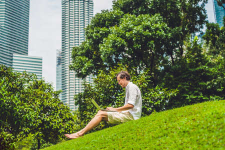 concep: Man businessman or student in casual dress using laptop in a tropical park on the background of skyscrapers. Dressing in a white shirt, beige shorts. Young handsome businessman in casual clothes is sitting outside a business district. Mobile Office concep