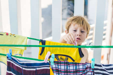 A little boy helps her mother to hang up clothes.