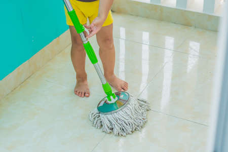 kid boy cleaning room, washing floor with mop. Little home helper. Montessori concept.