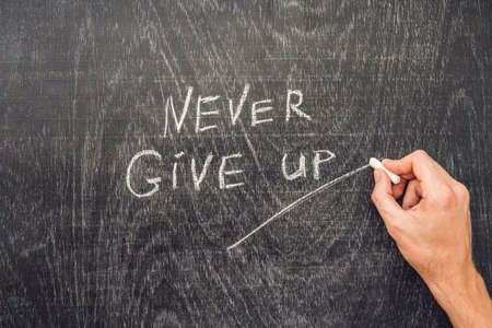 Never give up words written on the chalkboard. Standard-Bild