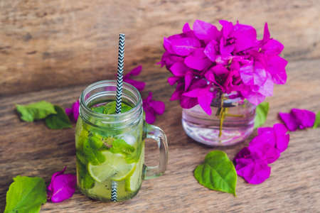 Spring purple flowers and spring mojito drink on an old wooden background.