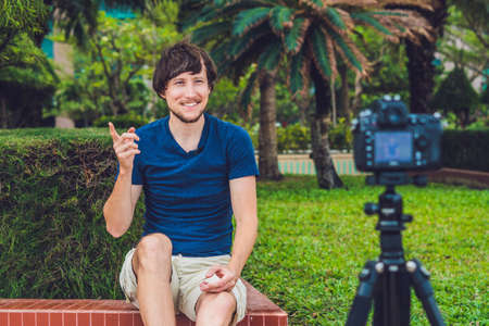 Young man blogger records video in front of the camera in the park. Stock Photo