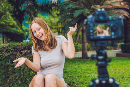 discus: A young female blogger is leading her video blog in front of the camera in the park. Stock Photo