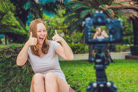 A young female blogger is leading her video blog in front of the camera in the park. Stock Photo