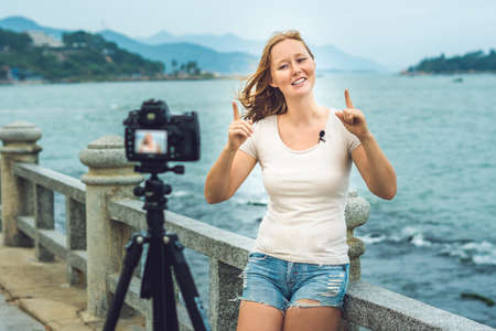 discus: A young woman blogger leads her video blog in front of a camera by the sea. Stock Photo