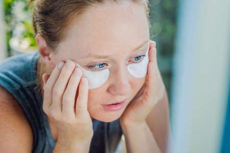 undereye: Portrait of Beauty Red-haired woman with eye patches showing an effect of perfect skin.
