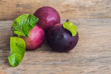 fresh Chrysophyllum cainito fruits on wood background.
