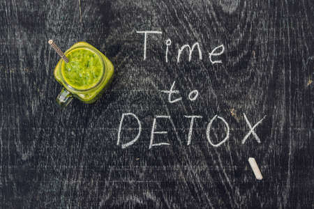 drench: TIME TO DETOX chalk inscription on the wooden table and Green smoothies made of spinach. Healthy eating and sports concept. Stock Photo