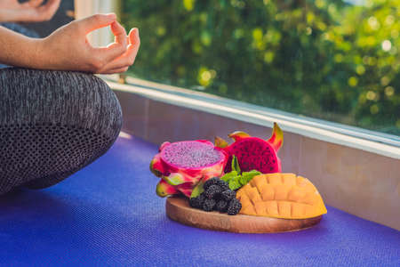 hand of a woman meditating in a yoga pose, sitting in lotus with fruits in front of her dragon fruit, mango and mulberry.