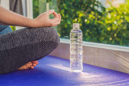 hand of a woman meditating in a yoga pose on a rug for yoga and a bottle of water.