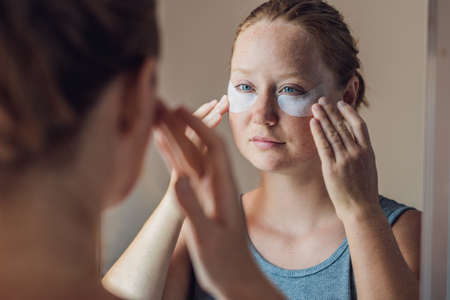 undereye: Portrait of Beauty Red-haired woman with eye patches showing an effect of perfect skin. Spa Girl.