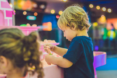Boy playing with kinetic sand in preschool. The development of fine motor concept. Creativity Game concept. Stock Photo