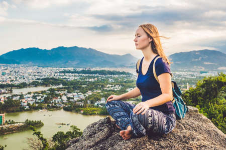 Young woman meditating over ancient city landscape on sunrise Copy space.