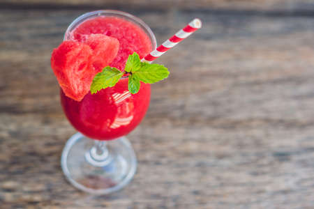 sliced watermelon: Healthy watermelon smoothie with mint and striped straws on a wood background.