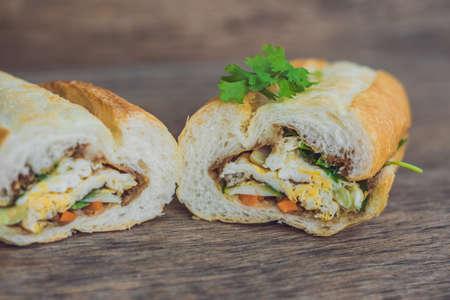 mi: A delicious Vietnamese Bahn Mi sandwich on a wooden background.