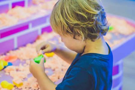plaything: Boy playing with kinetic sand in preschool. The development of fine motor concept. Creativity Game concept. Stock Photo