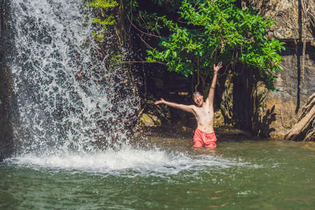 Side view of young man with arms standing against waterfall. Stock Photo