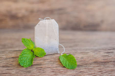 Tea bags on wooden background with fresh melissa, mint. Tea with mint concept.