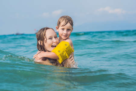 armbands: Young mother swimming and playing with male child boy in sea or ocean water sunny day outdoor on natural background, horizontal picture.