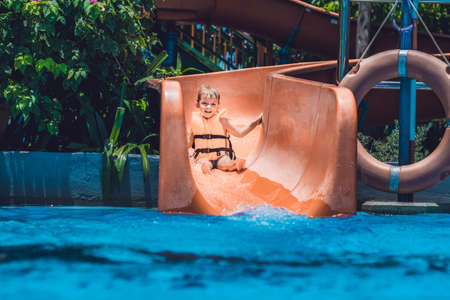 A boy in a life jacket slides down from a slide in a water park.