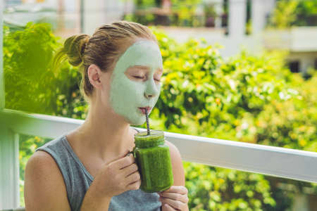 Spa Woman applying Facial green clay Mask. Beauty Treatments. Fresh green smoothie with banana and spinach with heart of sesame seeds. Love for a healthy raw food concept. Detox Concept.
