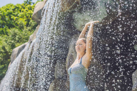 Young woman relaxing under a waterfall in aquapark. Vacation concept