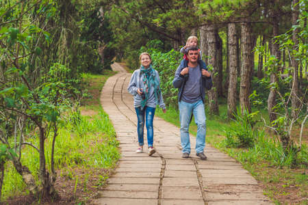6 7 year old: Family, mother, father and son, walking along the park path