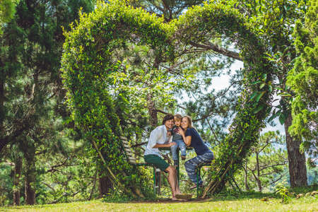 A loving family under a bush in the form of a heart. St. Valentines Day, love concept. Stock Photo