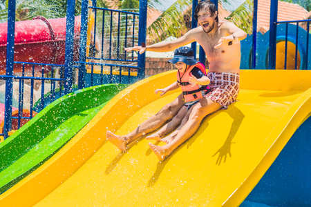 exhilarating: Father and son on a water slide in the water park. Stock Photo