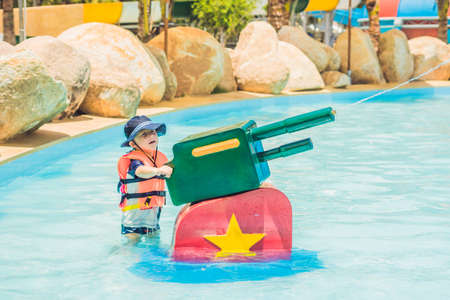 young child having fun with water cannon in aqua park. Stock Photo