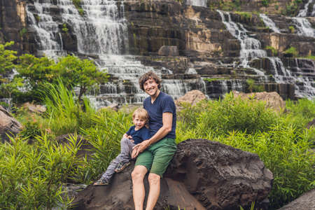dalat: Father and son hikers, tourists on the background of Amazing Pongour Waterfall is famous and most beautiful of fall in Vietnam. Not far from Dalat city estimate 45 Km. Dalat, Vietnam.