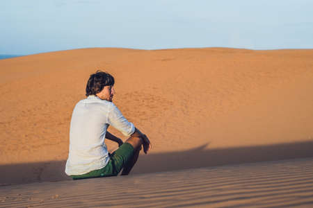 A man sits on the sand in the desert. Stock Photo