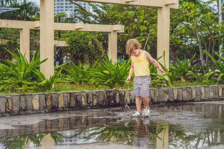 Little boy runs through a puddle. summer outdoor.