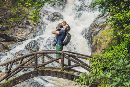 Father and son in the background of beautiful cascading Datanla waterfall In the mountain town Dalat, Vietnam.