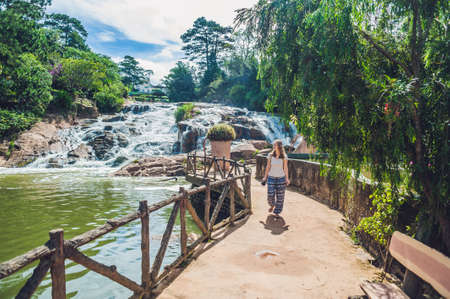 water feature: Young woman on the background of Beautiful Camly waterfall In Da Lat city,