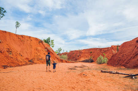 grand son: Father and son travelers in red canyon near Mui Ne, southern Vietnam. Traveling with children concept.
