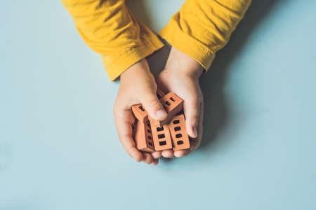 테이블에 진짜 작은 점토 벽돌 놀고 아이의 손 닫습니다. 유아 재미와 진짜 작은 점토 벽돌 건물. 조기 학습. 장난감 개발. 건설 개념입니다.