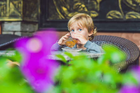 cup four: Cute little boy drinking tea in cafeteria.