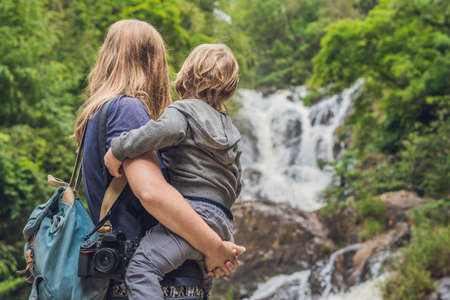 travel features: Mother and son in the background of beautiful cascading Datanla waterfall In the mountain town Dalat, Vietnam. Stock Photo