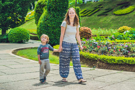 many babies: Mom and son are walking in the tropical park.